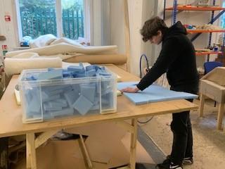 Photo below of Evan, new apprentice, cutting foam